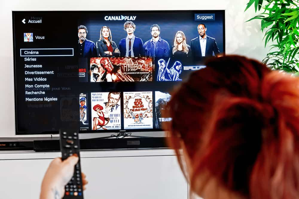 Woman holding a television remote control and watching homepage of canalplay. CanalPlay is a paid French Internet service for the distribution of video files