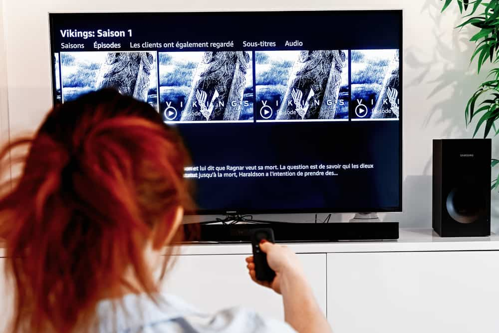 Woman holding a tv remote control In the process of selecting the viking success series proposed by Prime Video, a video-on-demand service