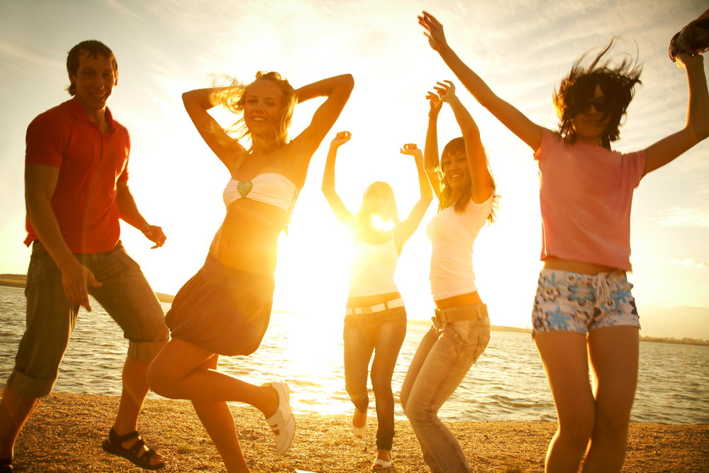 Group of happy young dancing at the beach on beautiful summer sunset