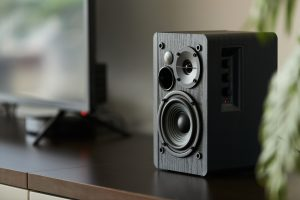 Bookshelf speaker with digital TV and set top box on a TV stand